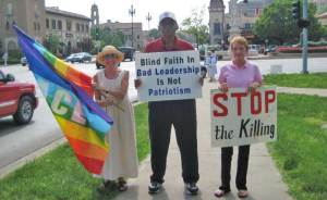 Dee Berry (on left) stands at a weekly peace rally with other Kansas City Greens, John Burris and Elise Kline
